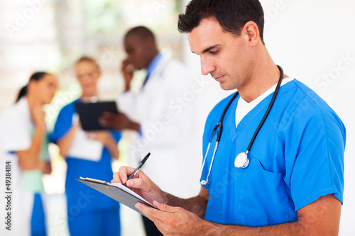 male medical worker writing report in hospital