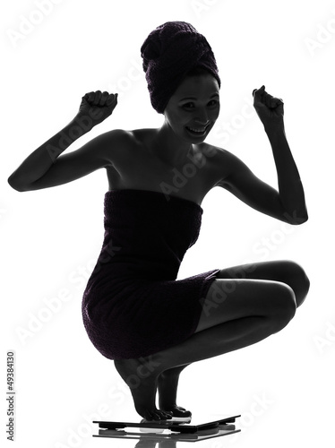 beautiful asian young woman happy on  weight scale silhouette