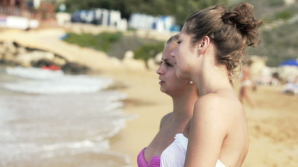 Girlfriends standing on the beach, super slow motion
