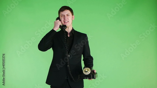 businessman talking on old phone angry