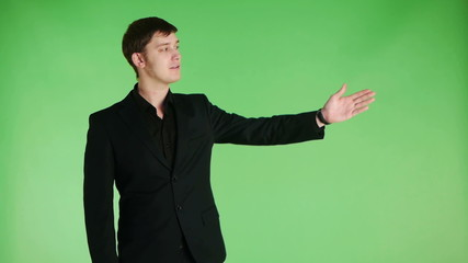 young businessman making a presentation on green background