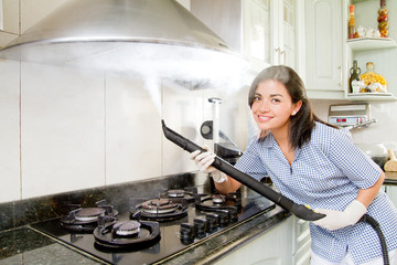 Smiling young woman cleaning kitchen