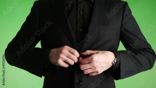 businessman buttoning a suit closeup