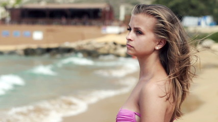 Pensive beautiful woman on the beach