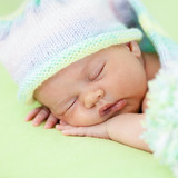 adorable baby weared cap sleeping on green