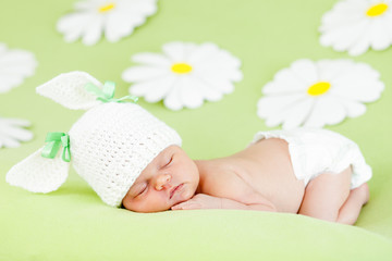 newborn baby girl sleeping on green meadow among flowers