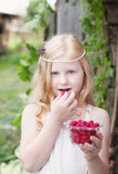 little girl holding raspberries
