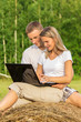 The young couple sits outdoors with the laptop