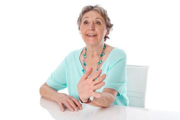 Ältere grauhaarige Frau hält einen Vortrag
