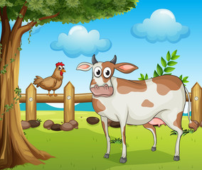 A cow, a hen and a beautiful landscape
