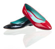Black and red patent leather pumps over white background