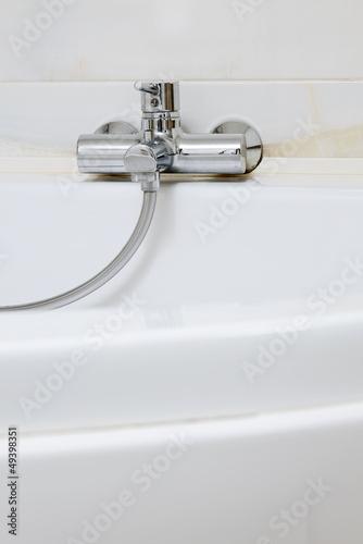 Modern metal faucet on white ceramic bathtub, interior detail