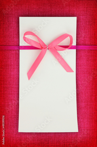 Empty card on pink fabric texture