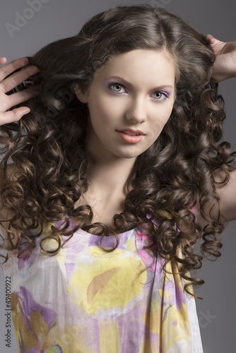 pretty brunette with curly hair smiles - 49400922