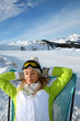 Woman in ski outfit relaxing in long chair