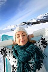 Woman in ski resort relaxing in long chair