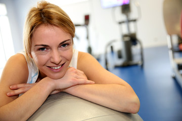 Portrait of fitness girl leaning on balance ball