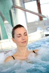 Woman enjoying hydrojet shower in spa pool