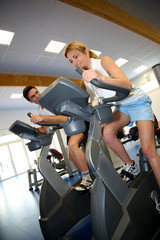 People exercising on bicycles in fitness gym
