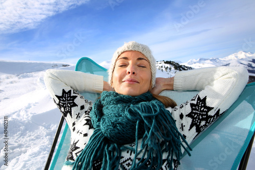 Woman in ski resort relaxing in long chair