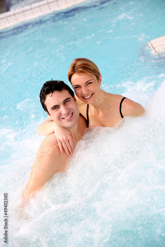 Couple enjoying jacuzzi in spa center