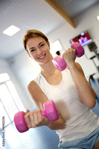 Happy woman in gym lifting dumbbells