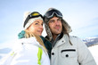 Portrait of couple of skiers looking at panorama