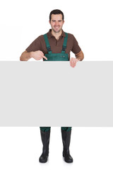 Happy young gardener presenting empty banner