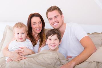 glückliche familie zu hause im bett