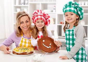 Little chef girls with their mother making a cake