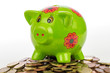 grünes Sparschwein auf Münzhaufen