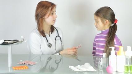 Pediatrician woman gives a little girl pill