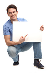 Young man pointing at blank board