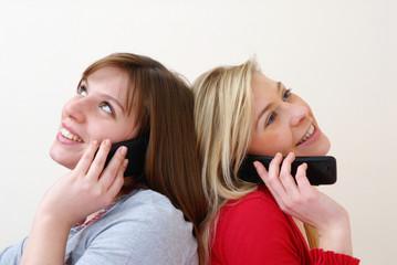 Dos mujeres conversando por teléfono celular.