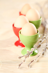 Eggs in red and green eggcups with catkins