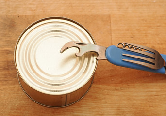 The old tin opener opening a can on wooden table