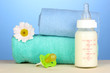 Baby bottle of milk with pacifier and towels on blue background