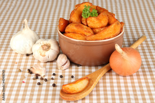 Appetizing village potatoes in bowl on beige tablecloth