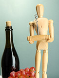 Mannequin with corkscrew and wine bottle, on grey background