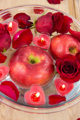 Apple with rose petals and heart candles in glass bowl