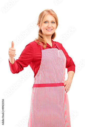 A female manual worker wearing an apron and giving thumb up