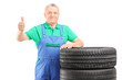 A mature worker posing on car tires and giving thumb up