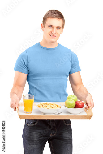 A smiling carrying a wooden tray with drinks and food