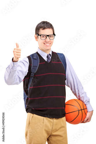 Male student with school bag holding a basketball and giving thu