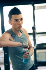 Young asian man having a rest drinking a beverage in the gym.