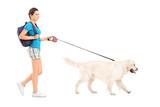 Full length portrait of a female student walking her dog