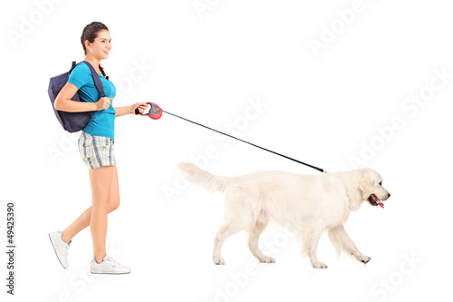 Full length portrait of a female student walking her dog