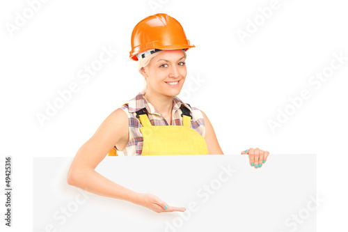Female manual worker standing behind blank panel and gesturing