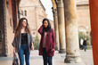 Two girls walking in Saint Stephen square, Bologna, Italy