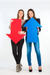Two beautiful women holding red and blue arrow, up and down